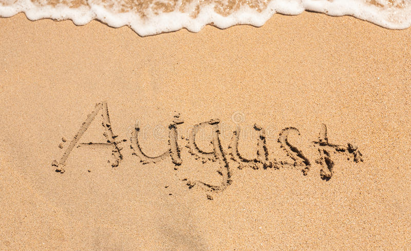 Word august on the sandy beach royalty free stock image