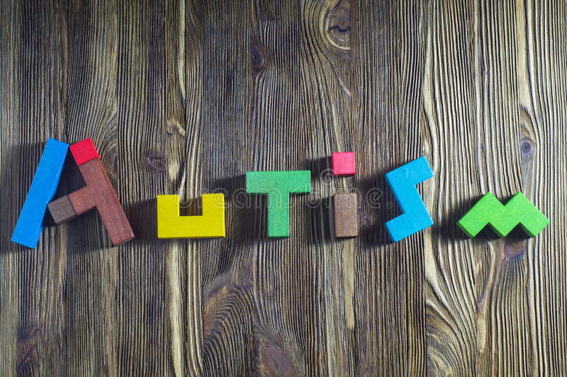Word Autism built of wooden puzzles on a wooden background. Concept of autism word royalty free stock photo