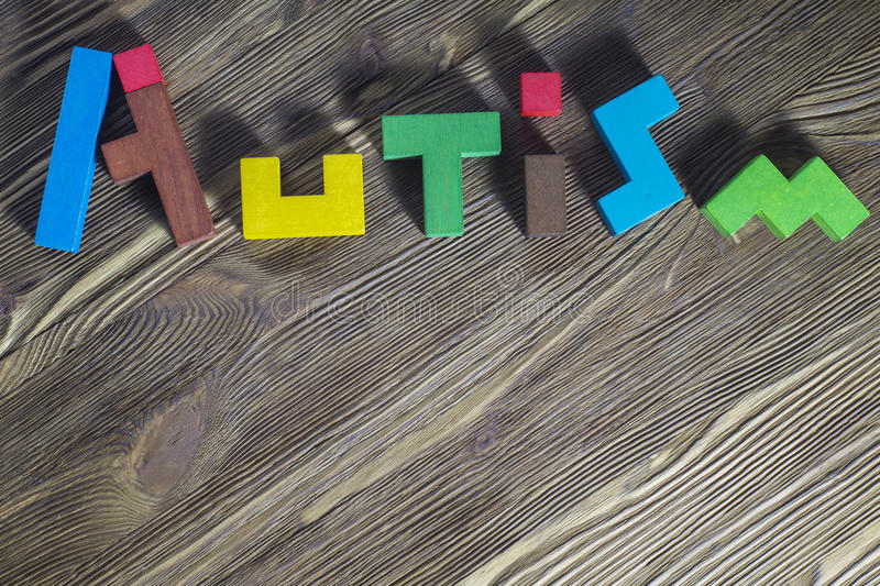 Word Autism built of wooden puzzles on a wooden background. Concept of autism word stock photo