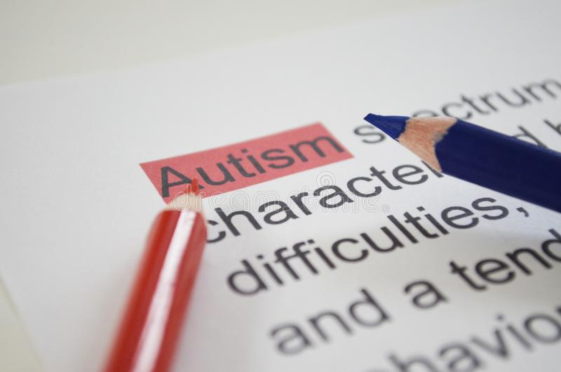 Word AUTISM , close up. Word AUTISM with colorful pencils underlined with red marker royalty free stock photos