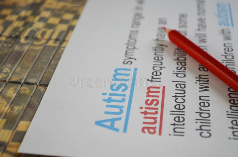 Word AUTISM , close up. Newspaper article and word AUTISM underlined with red and blue pencils royalty free stock images