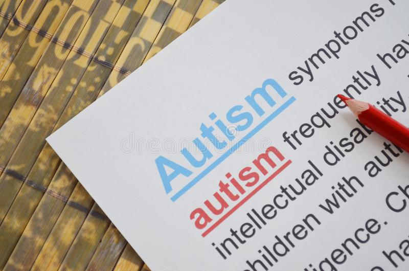 Word AUTISM , close up. Newspaper article and word AUTISM underlined with red and blue pencils stock images