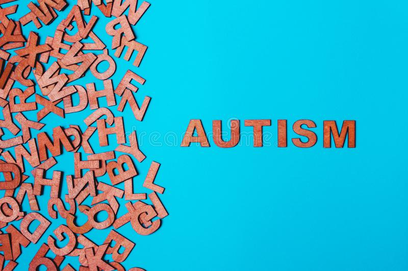 The word Autism from wooden letters on a blue background. The problem is in socialization, communication royalty free stock photos
