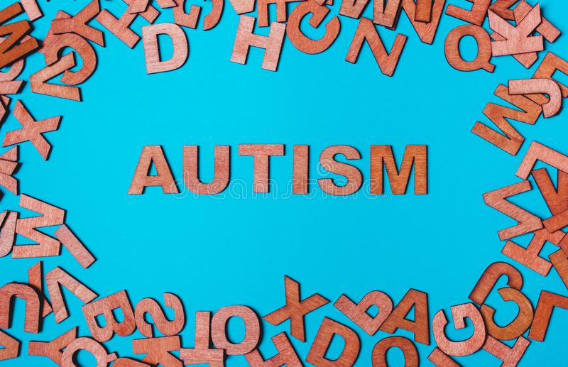 Word Autism from wooden letters on a blue background. The word Autism from wooden letters on a blue background. The problem is in socialization, communication stock photo