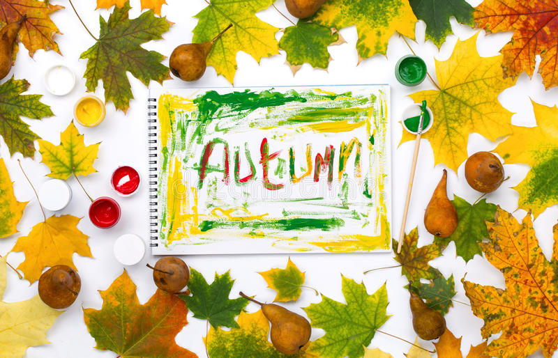 Word autumn in an album with autumn leaves and pear stock image