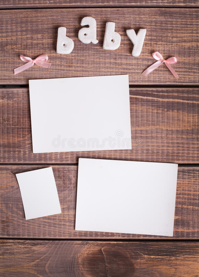 Word baby and white frame photo. On wood background stock photos