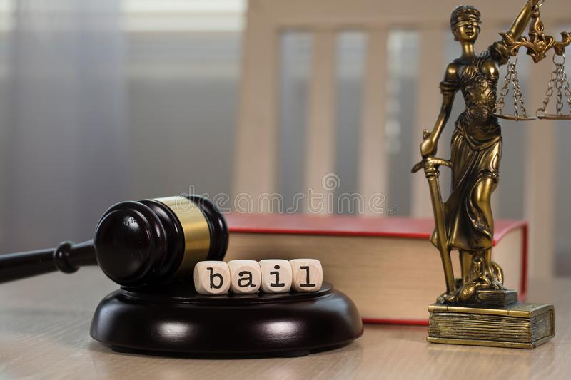 Word BAIL composed of wooden dices. Wooden gavel and statue of Themis in the background. Word BAIL composed of wooden dices.  Wooden gavel and statue of Themis royalty free stock photos