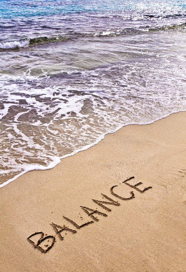 Word BALANCE written on beach sand, with sea waves in background. Peace concept royalty free stock photo