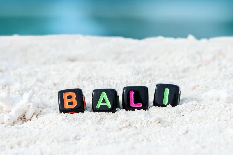 Word Bali wordt gemaakt van multicolored brieven op sneeuwwit zand tegen het blauwe overzees stock foto