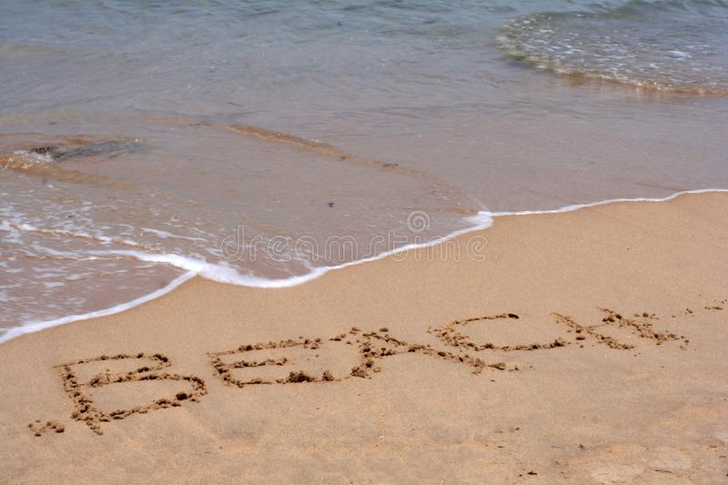 The word BEACH written in sand stock photography