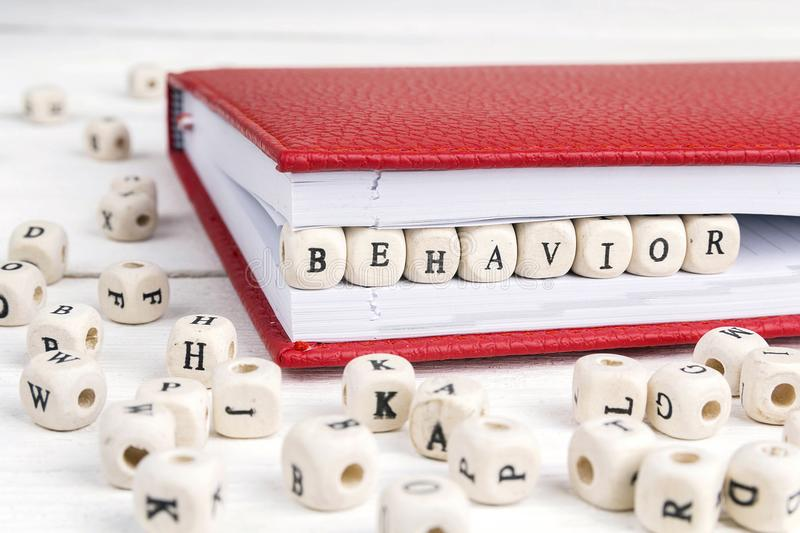 Word Behavior written in wooden blocks in notebook on white wood. Word Behavior written in wooden blocks in red notebook on white wooden table royalty free stock photography