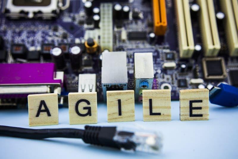 Word BEHENDIG op de houten blokken met computertechnologie mainboard achtergrond IT de achtergrond van het conceptenbeeld stock foto's