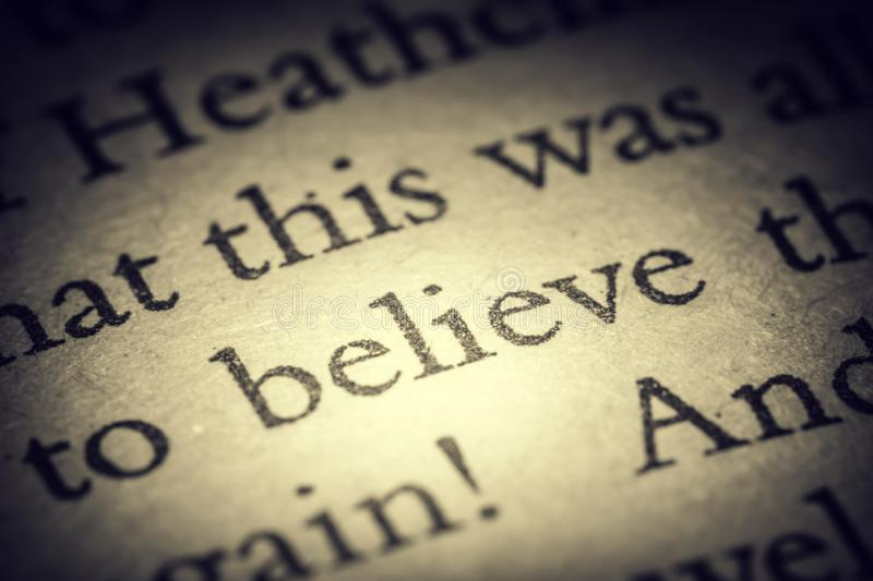 The word believe on old page in a open book close-up macro. Vintage, grunge, old, retro style photo stock images
