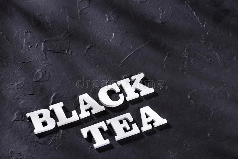 Word black tea in wood letters - Camellia sinensis.  stock image