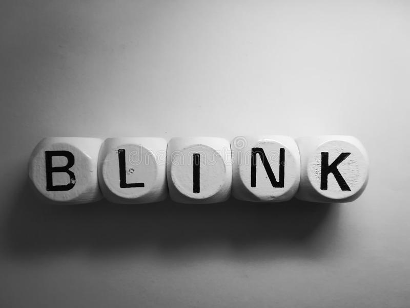 Word blink spelled on dice. Spelling of the word blink using dice on white background royalty free stock photography