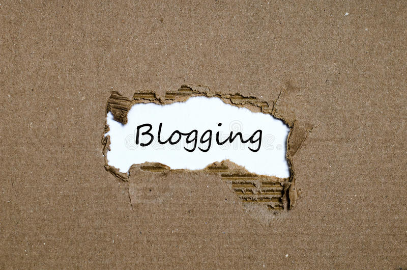 The word blogging appearing behind torn paper royalty free stock photos