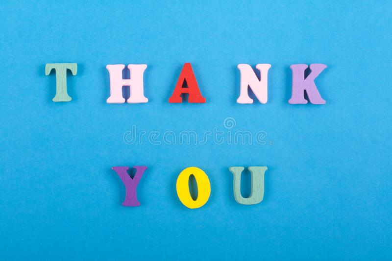 THANK YOU word on blue background composed from colorful abc alphabet block wooden letters, copy space for ad text. Word on blue background composed from stock images