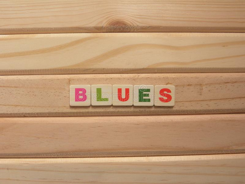 Word Blues. On wood background stock photos