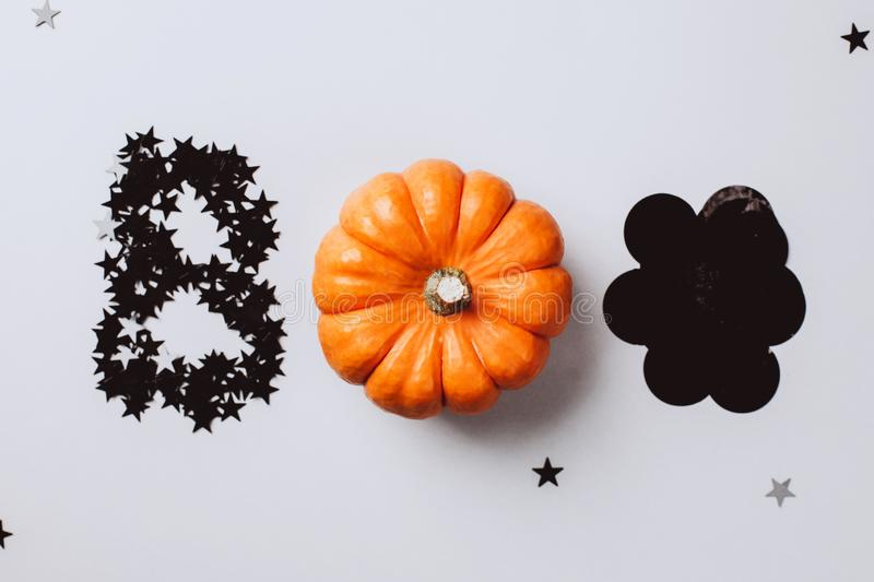 Word Boo is made from little pumpkin, silver stars confetti and black decor. Halloween party concept. Flat lay style. Top view stock image