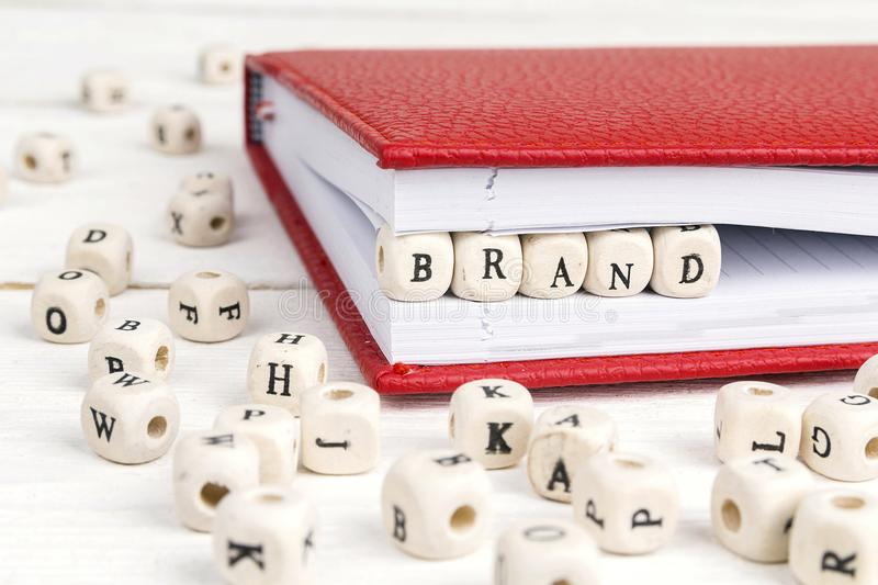 Word Brand written in wooden blocks in notebook on white wooden stock images