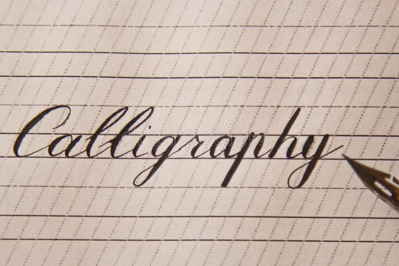 Word calligraphy is written with an ink pen on a white paper sheet with stripes drawn. stationery close up top view. spelling. Lessons and caligraphy exercises stock photo