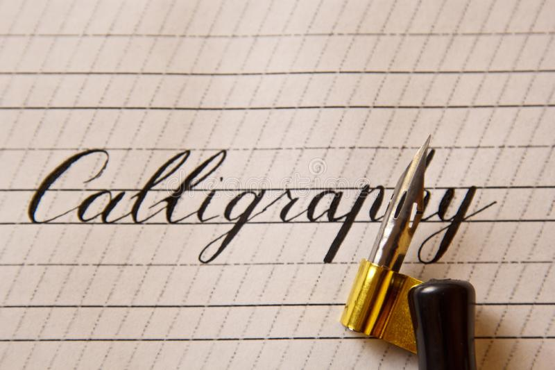 Word calligraphy is written with an ink pen on a white paper sheet with stripes drawn. stationery close up top view. spelling. Lessons and caligraphy exercises stock image