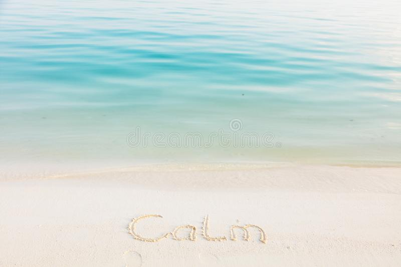 The Word Calm Written in the Sand on a Beach with blue sea background.  stock images