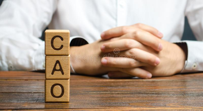 The word CAO and a man with locked hands. Chief Accounting Officer. Vacancy and duties of a specialist. Manage taxes and payroll. Develop and upgrade finance royalty free stock photos