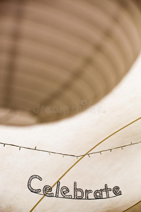 The word celebrate in bent metal artwork with paper light shades royalty free stock photos