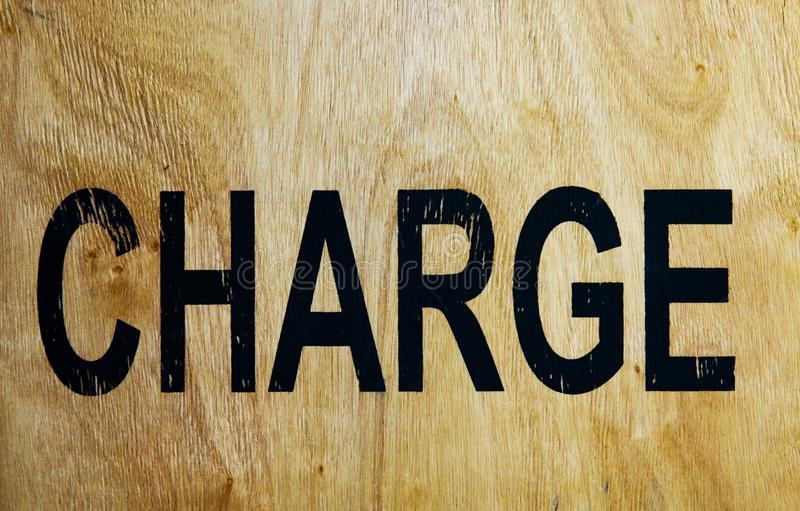 Word charge printed on old brown wood box stock image