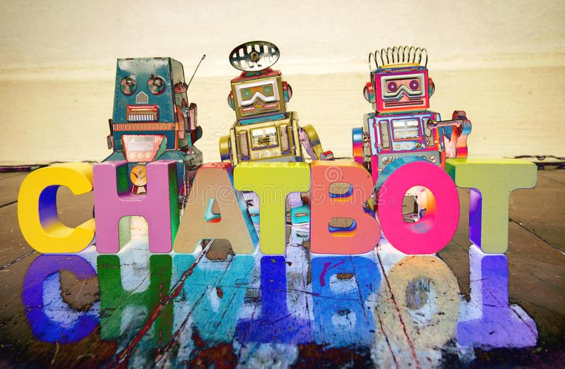 The word CHAT BOT with wooden letters and retro toy robots on royalty free stock photography