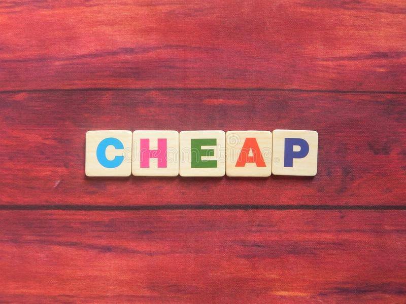 Word Cheap on wood. Background stock photos