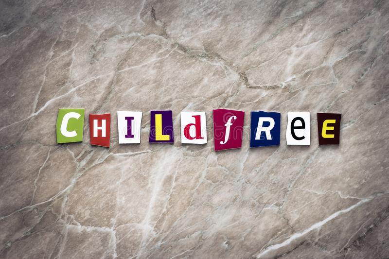 Word child free of cut letters on brown background. Ideology concept. Headline, writing text child-free on the banner. Abstract ca. Rd with an inscription stock photo