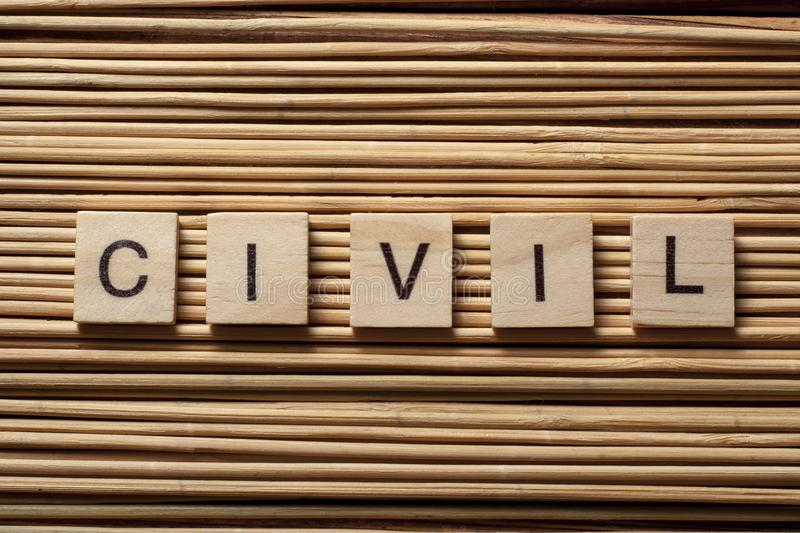Word CIVIL on wood cubes at wooden background. stock image