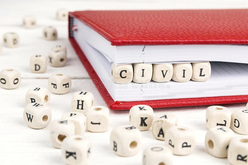 Word Civil written in wooden blocks in notebook on white wooden stock photos
