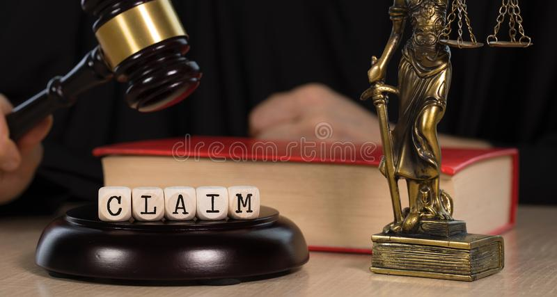 Word CLAIM composed of wooden dices. Wooden gavel and statue of Themis in the background. Word CLAIM composed of wooden dices.  Wooden gavel and statue of Themis royalty free stock photos