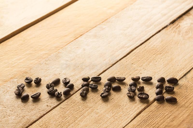 Word coffee written by coffee beans on wooden background stock photography