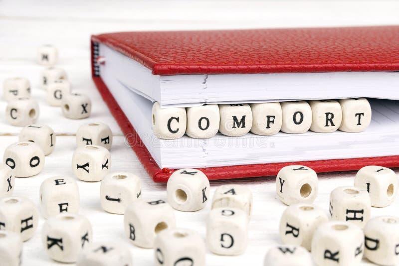Word Comfort in houten blokken in rood notitieboekje op wit w wordt geschreven dat stock afbeeldingen