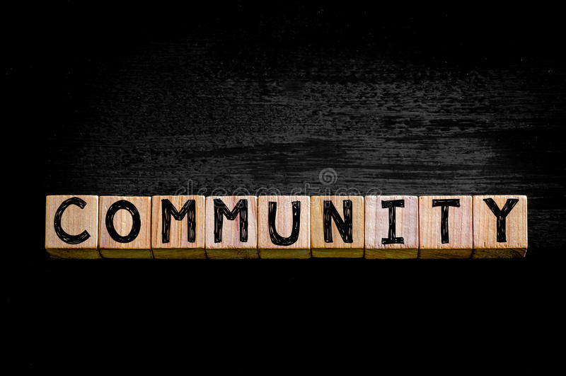 Word COMMUNITY isolated on black background. Word COMMUNITY. Wooden small cubes with letters isolated on black background with copy space available. Concept stock image