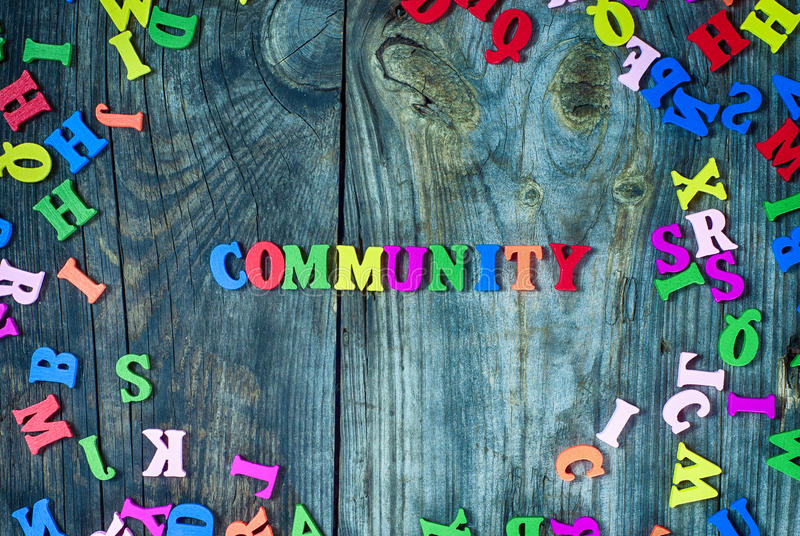 Word community from small multi-colored letters. Gray wooden background royalty free stock photography