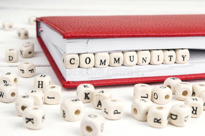 Word Community written in wooden blocks in red notebook on white. Wooden table. Wooden abc stock photography