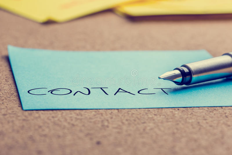 Word contact op een post-itdocument stock afbeelding