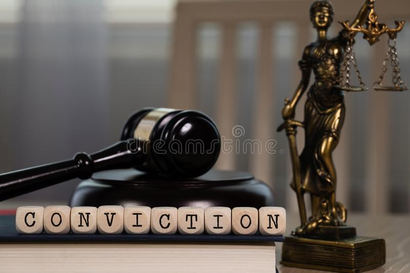 Word CONVICTION composed of wooden dices. Wooden gavel and statue of Themis in the background. Closeup, ancient, greek, titaness, book, chair, concept, court stock image