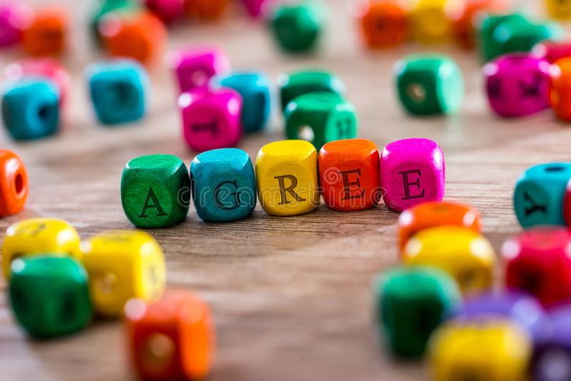 Word created with colored wooden cubes on desk. Agree - word created with colored wooden cubes on desk stock images