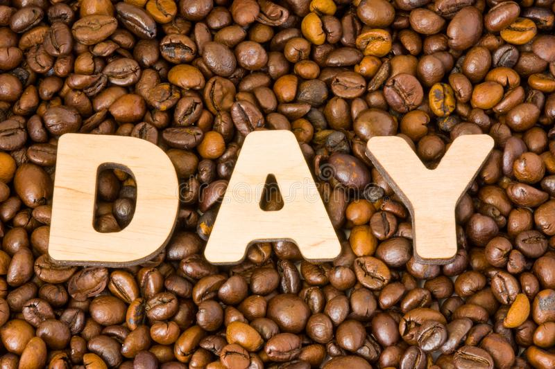 Word of Day composed of large wooden letters on background of roasted brown coffee beans. Concept photo of International Coffee Da stock image