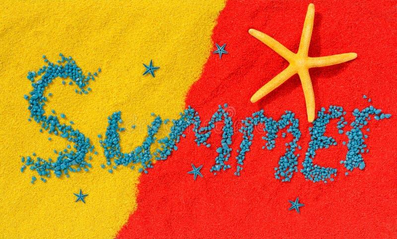 Word de 'zomer 'wordt opgemaakt van arduinstenen op kleurenzand stock afbeeldingen