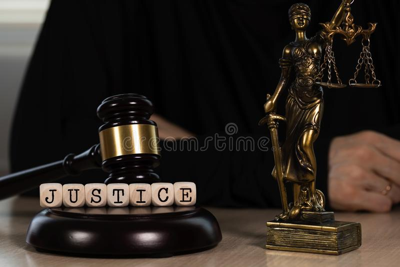 Word de RECHTVAARDIGHEID uit houten wordt samengesteld die dobbelt Houten hamer en standbeeld van Themis op de achtergrond royalty-vrije stock afbeelding