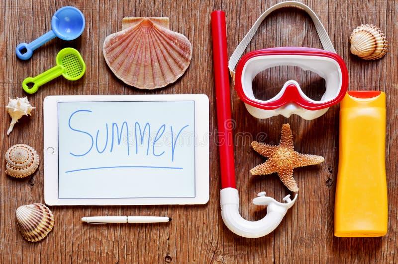 Word de zomer in een tablet wordt geschreven en het de zomermateriaal op een plattelander die streven na royalty-vrije stock foto