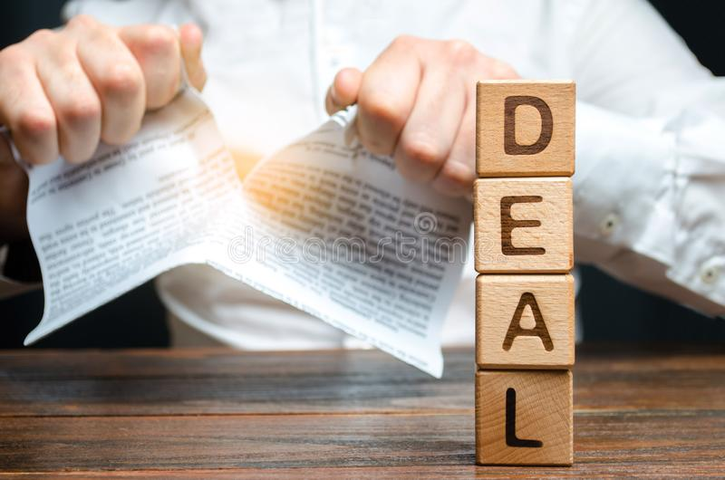 The word deal and businessman is breaking a contract in the background. Contract break unilaterally. Violation and default. Conflict. Termination of employment stock photos