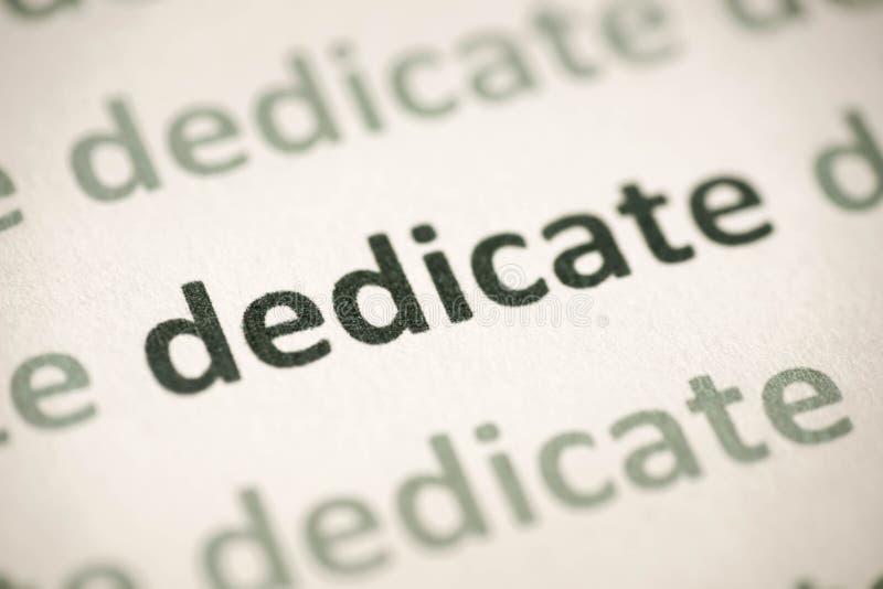 Word dedicate printed on paper macro. Word dedicate printed on white paper macro stock images
